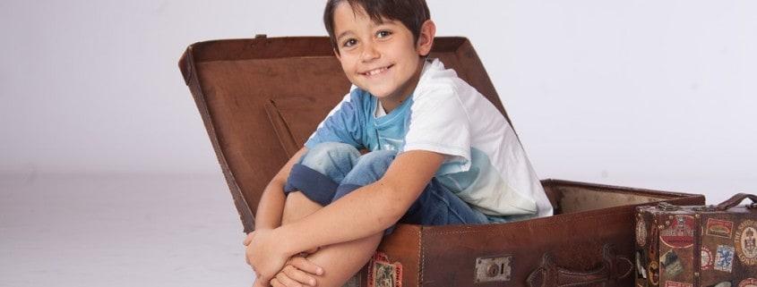 Gabriel sitzt in einem großen Koffer