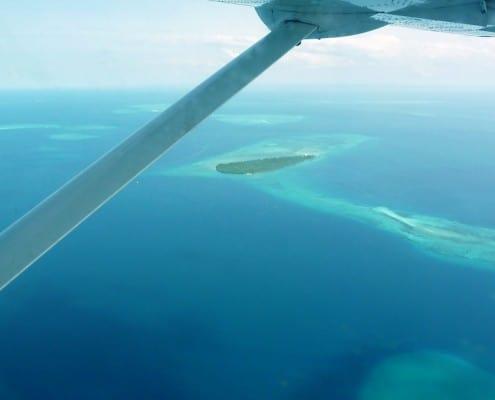 Luftbild aus einem kleinen Flugzeug auf das Meer von Afrika mit kleiner Insel