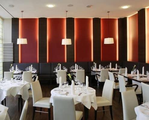 Restaurant mit gedeckten Tischen mit roter beleuchteter Wand im NH Horn