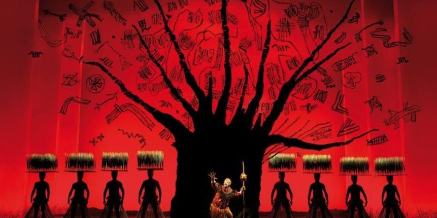 Bühnenbild mit Baum und Gras im Hinterggrund eines Sängers von König der Löwen