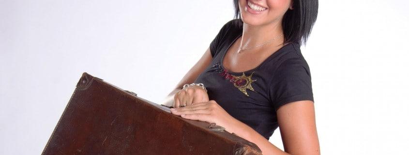 Sabrina mit großem braunen Koffer in der Hand