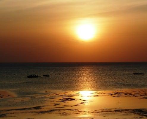 atemberaubende rote Sonnenuntergangsstimmung spiegelt sich im Meer von Sansibar