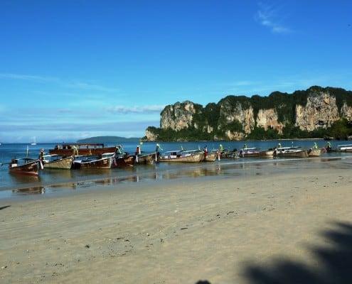 viele Longtailboote am Strand von Railay Beach in Thailand mit grün bewachsenen Bergen und schönem Wetter
